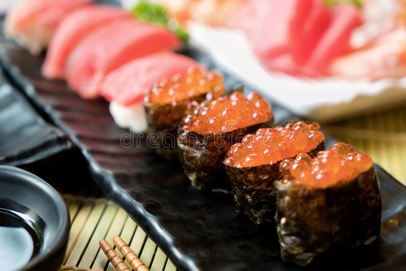 Sushi with chopsticks and soy sauce. Sushi roll japanese food in restaurant. Salmon roe Sushi set with salmon, vegetables, flying stock photos