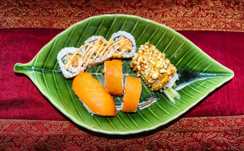 Sushi clasificado en una placa foliforme verde stting en un corredor del rojo y del oro imágenes de archivo libres de regalías
