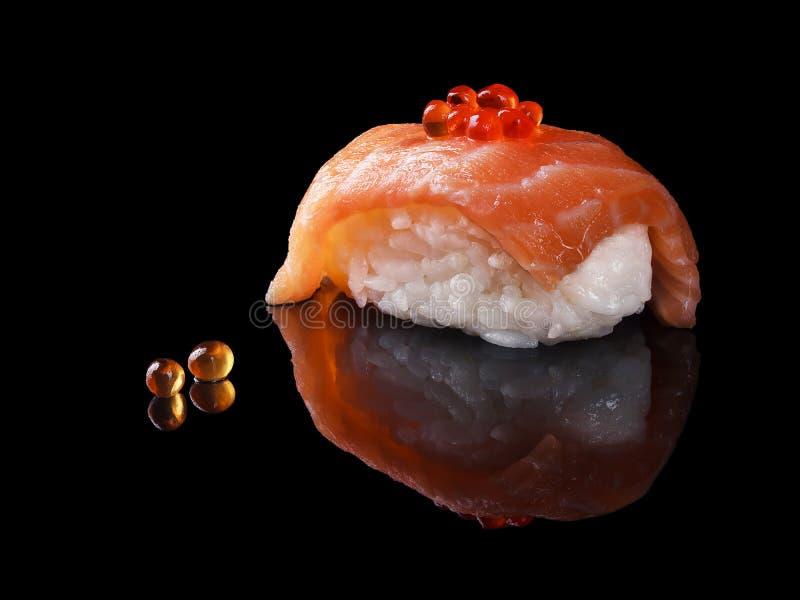 Sushi con los salmones en un fondo negro foto de archivo