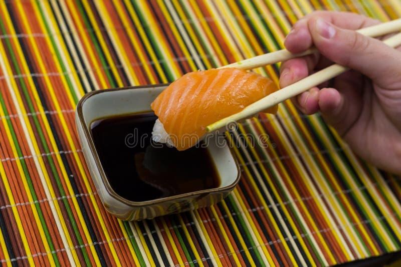 Sushi con los salmones en una porción del arroz en el fondo de una lona de bambú foto de archivo libre de regalías