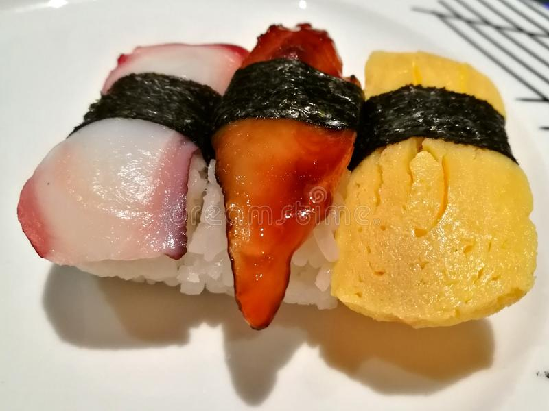 Sushi. Cooked vinegared rice topped with octopus, eel and egg stock image