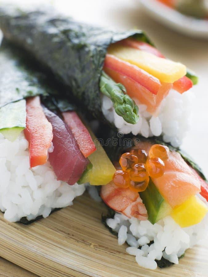 Sushi de fruits de mer roulés trois par mains et de légume images libres de droits