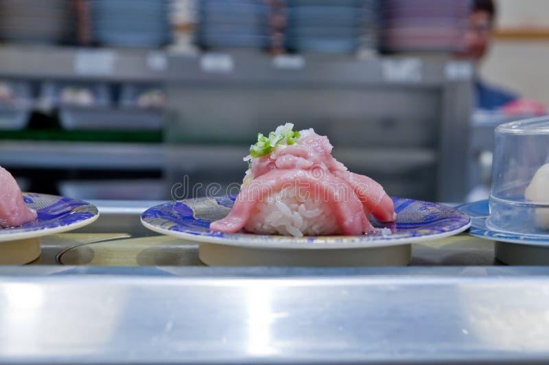 Sushi de Nigiri con el atún en un transportador en un restaurante fotos de archivo libres de regalías