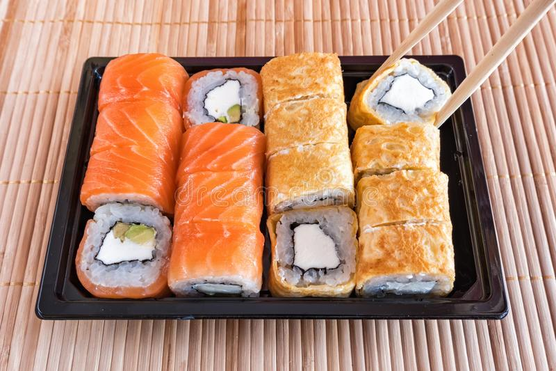 Sushi del rollo de Philadelphia con los salmones, el atún, el aguacate, el queso cremoso y el rollo en la tortilla Menú del sushi foto de archivo
