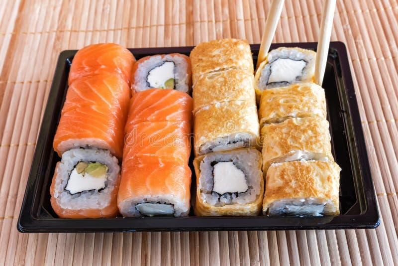 Sushi del rollo de Philadelphia con los salmones, el atún, el aguacate, el queso cremoso y el rollo en la tortilla Menú del sushi fotografía de archivo libre de regalías