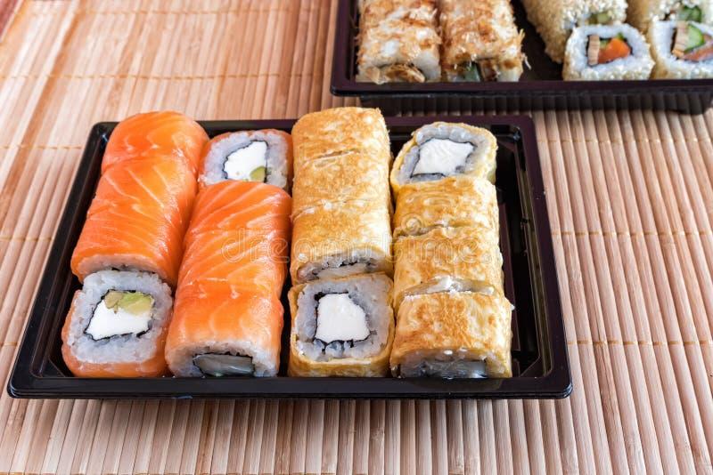 Sushi del rollo de Philadelphia con los salmones, el atún, el aguacate, el queso cremoso y el rollo en la tortilla Menú del sushi imagen de archivo libre de regalías