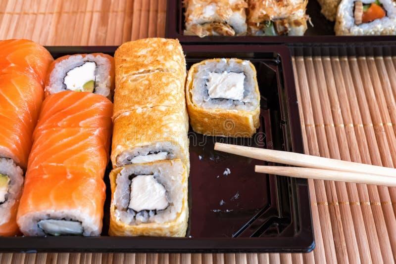 Sushi del rollo de Philadelphia con los salmones, el atún, el aguacate, el queso cremoso y el rollo en la tortilla Menú del sushi fotografía de archivo
