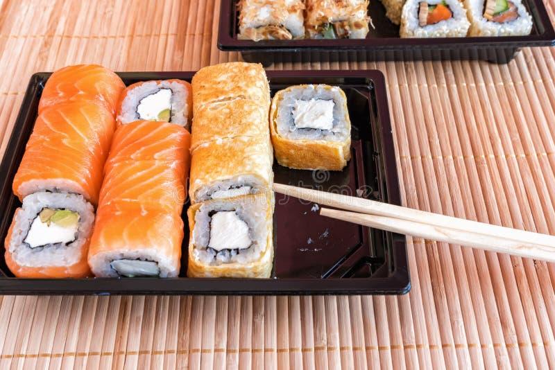 Sushi del rollo de Philadelphia con los salmones, el atún, el aguacate, el queso cremoso y el rollo en la tortilla Menú del sushi imagen de archivo