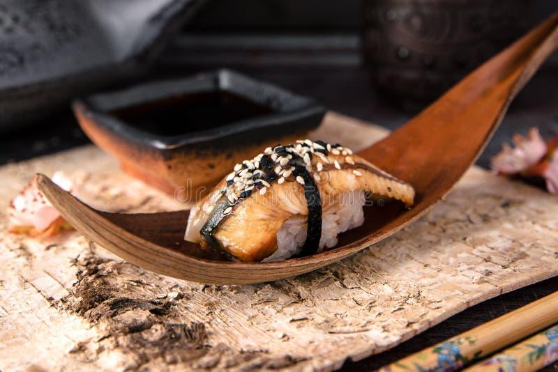 Sushi delicioso da enguia do sushi de Nigiri da enguia de Unagi Prato decorado com um ramo das flores de cerejeira imagens de stock royalty free