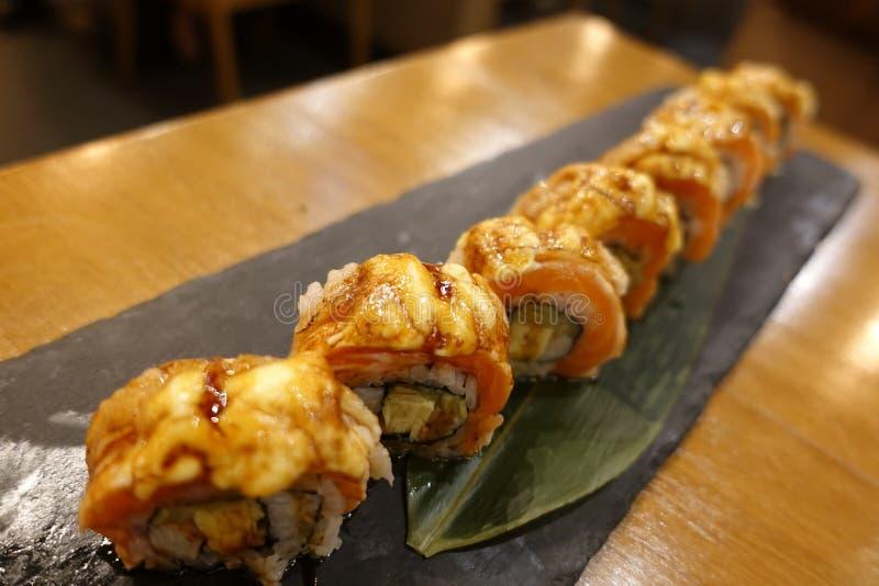 Sushi delicioso exclusivo con el top de color salmón de la parrilla en rap japonés del arroz por la alga marina Tradición japones imagenes de archivo