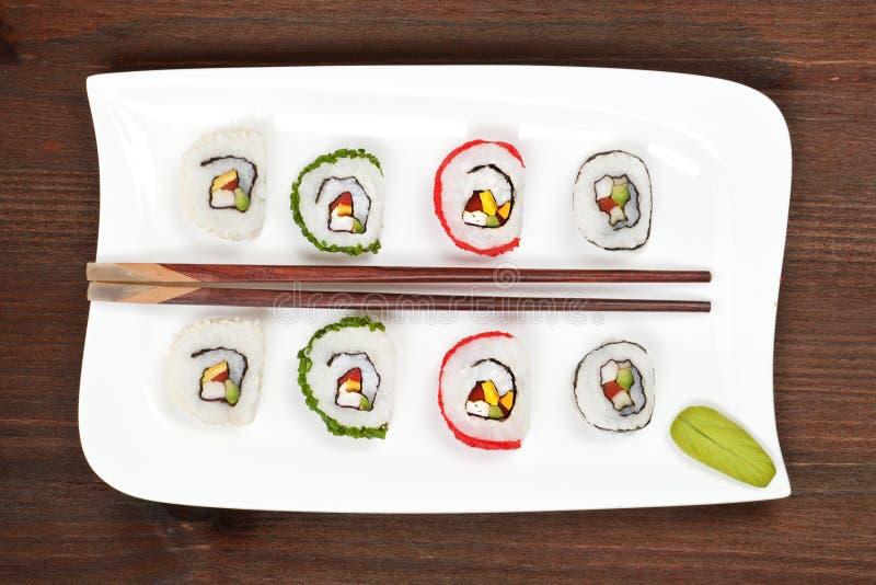 Sushi di Maki sulla zolla bianca con le bacchette. fotografia stock libera da diritti