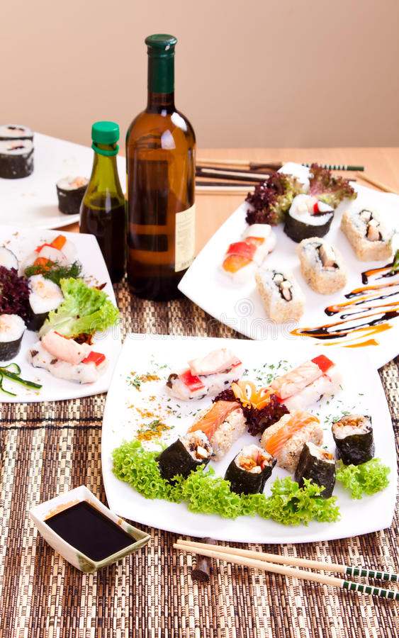 Sushi for dinner. Portion of nicely arranged sushi rolls on table with brown mat royalty free stock images