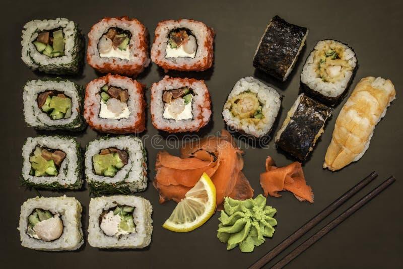 Sushi e rolos de sushi, nigiri do sushi na placa de pedra no fundo escuro fotos de stock