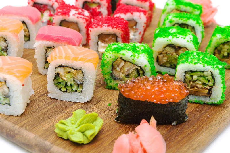Sushi e rolos diferentes em uma placa de estaca imagem de stock