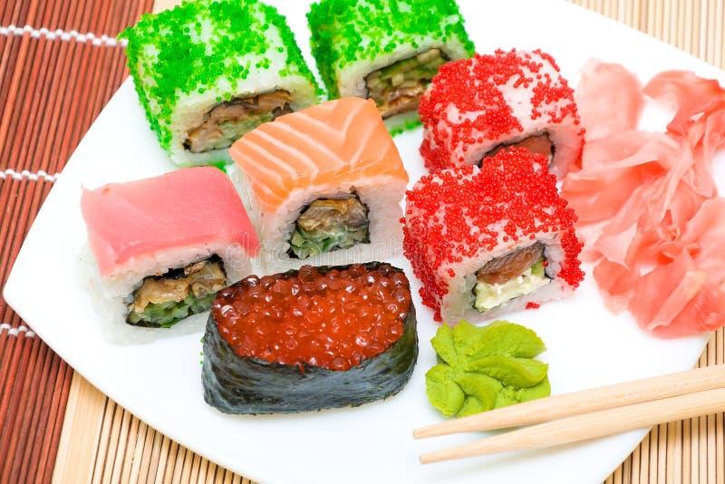 Sushi e rolos, gengibre conservado e wasabi em uma placa. horizonta foto de stock royalty free