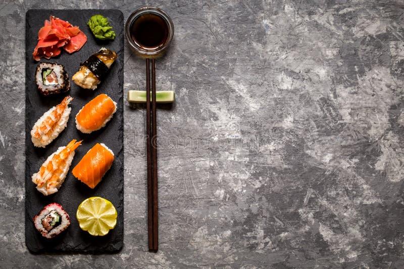 Sushi e rotoli di sushi, nigiri dei sushi sul piatto di pietra su fondo scuro, wasabi della senape fotografia stock
