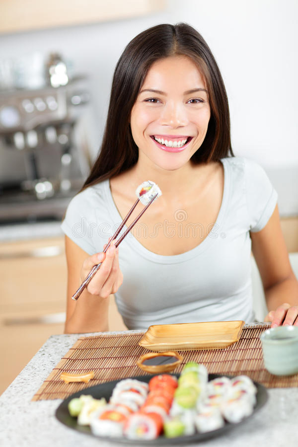 Sushi eating young Asian woman - smiling happily royalty free stock photos