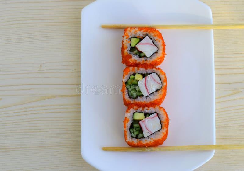Sushi en maträtt av traditionell japansk kokkonst som lagas mat från ris, kalvar av en lax, crabmeat, avokadot och en gurka arkivfoto