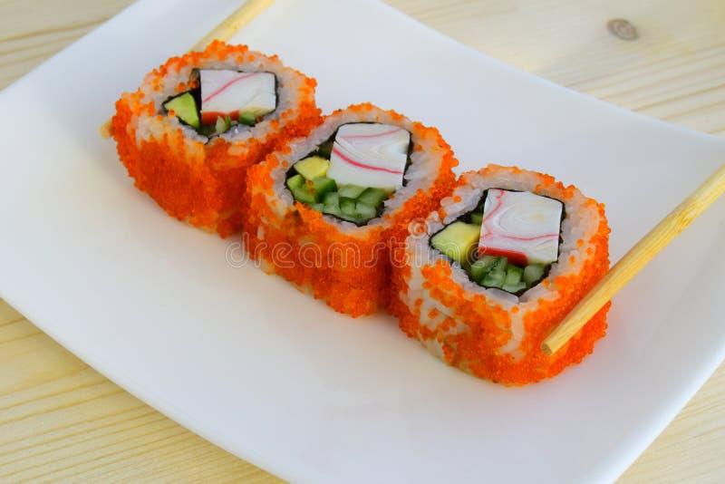 Sushi en maträtt av traditionell japansk kokkonst som lagas mat från ris, kalvar av en lax, crabmeat, avokadot och en gurka royaltyfria foton