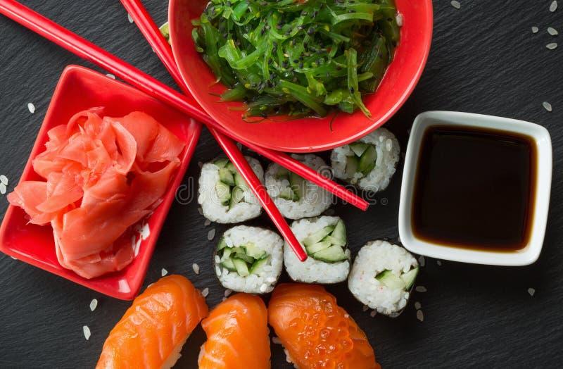 Sushi et petits pains avec de la salade de mer verte sur une table d'ardoise image libre de droits