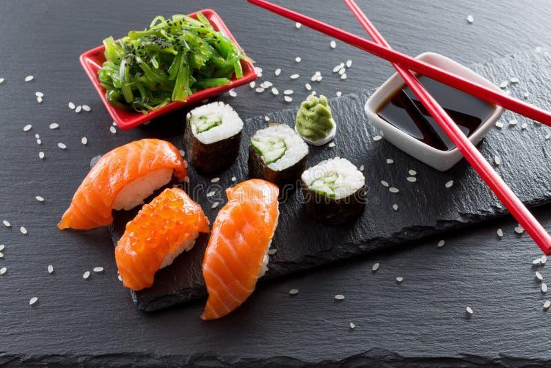 Sushi et petits pains avec de la salade de mer verte sur une table d'ardoise images stock