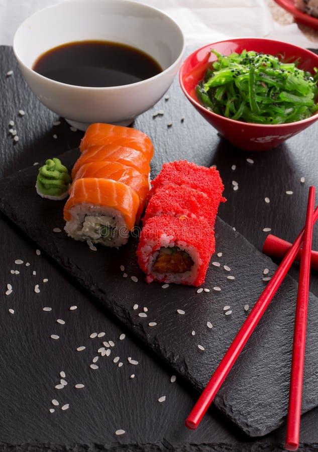Sushi et petits pains avec de la salade de mer verte sur une table d'ardoise photo stock