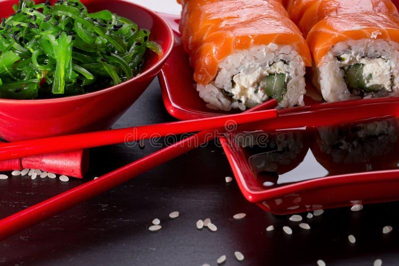 Sushi et petits pains avec de la salade de mer verte sur une table d'ardoise photos stock