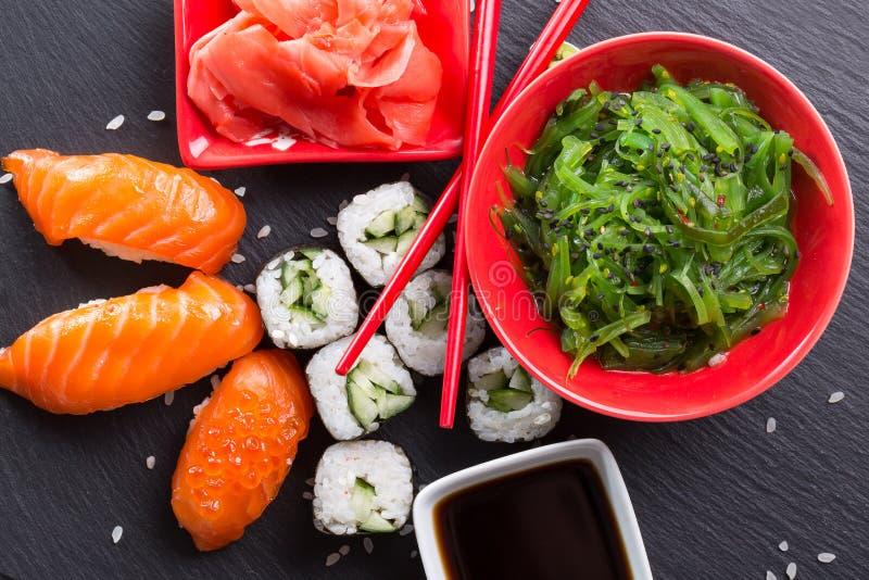 Sushi et petits pains avec de la salade verte sur la table d'ardoise images stock