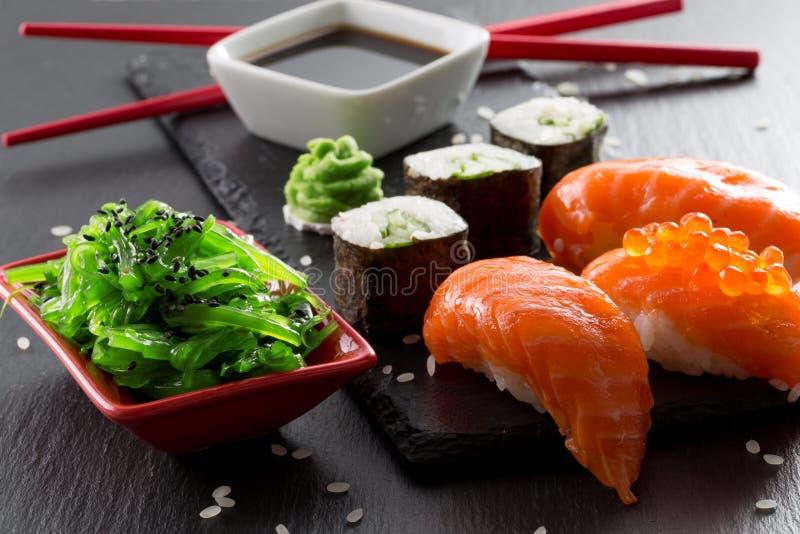 Sushi et petits pains avec le seasalad vert sur une table d'ardoise images stock