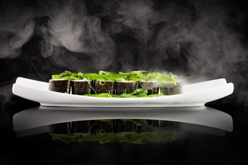 Sushi et salade verte d'algue du plat blanc image stock