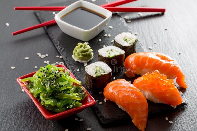Sushi et salade verte d'algue sur une table d'ardoise images stock