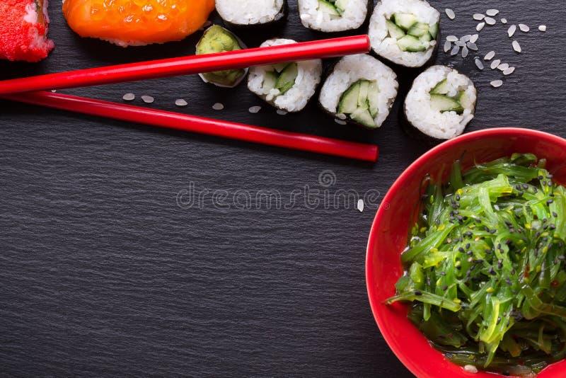 Sushi et salade verte d'algue sur une table d'ardoise photographie stock