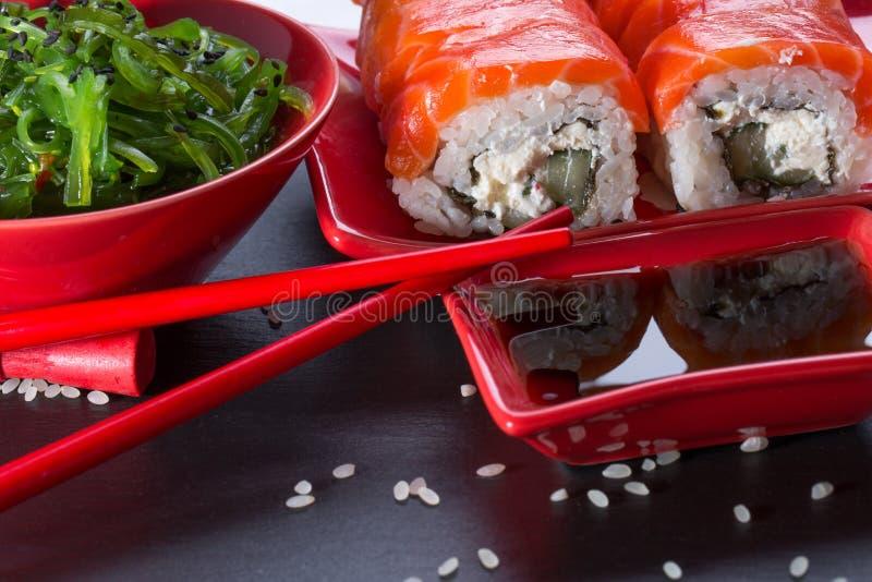 Sushi et salade verte d'algue sur une table d'ardoise photos libres de droits