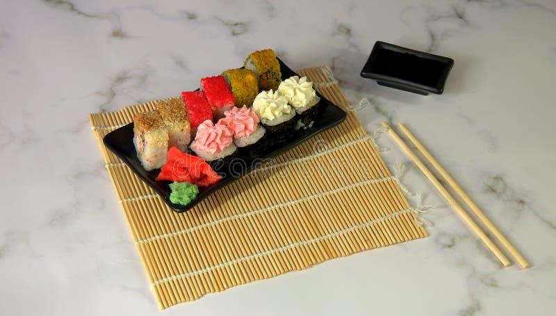 Sushi fijado con el jengibre rojo y el wasabi en una servilleta de bambú, cuenco con la salsa de soja y palillos Primer imagen de archivo libre de regalías