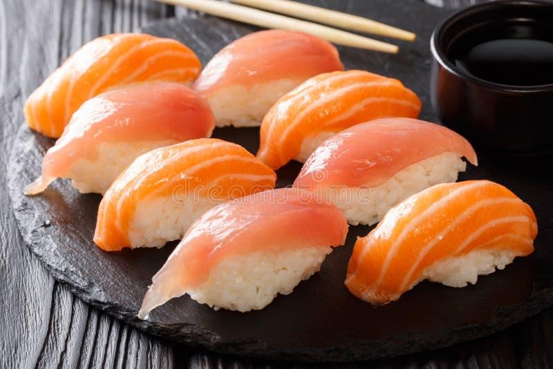Sushi fraîchement cuits avec les saumons et le thon, sauce de soja, baguettes photographie stock