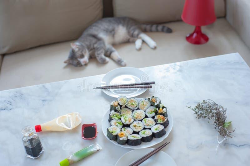 Sushi futo-maki casero en primer plano y gato en segundo plano imagenes de archivo