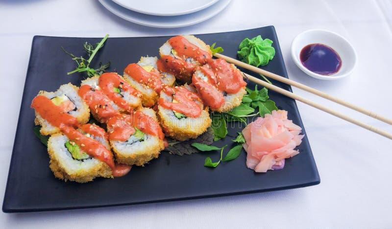 Sushi - Futomaki di color salmone fritto nel grasso bollente immagini stock