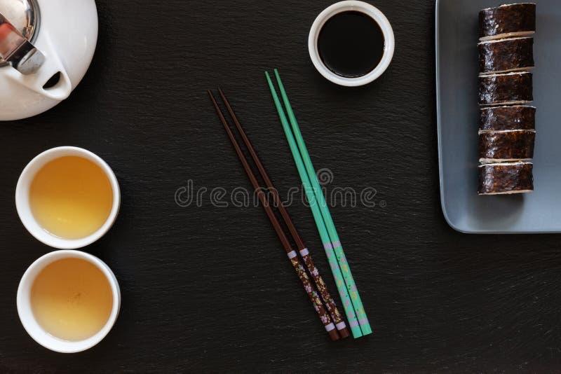 Sushi giapponesi con la salsa di soia sul piatto grigio con i bastoncini fotografia stock libera da diritti