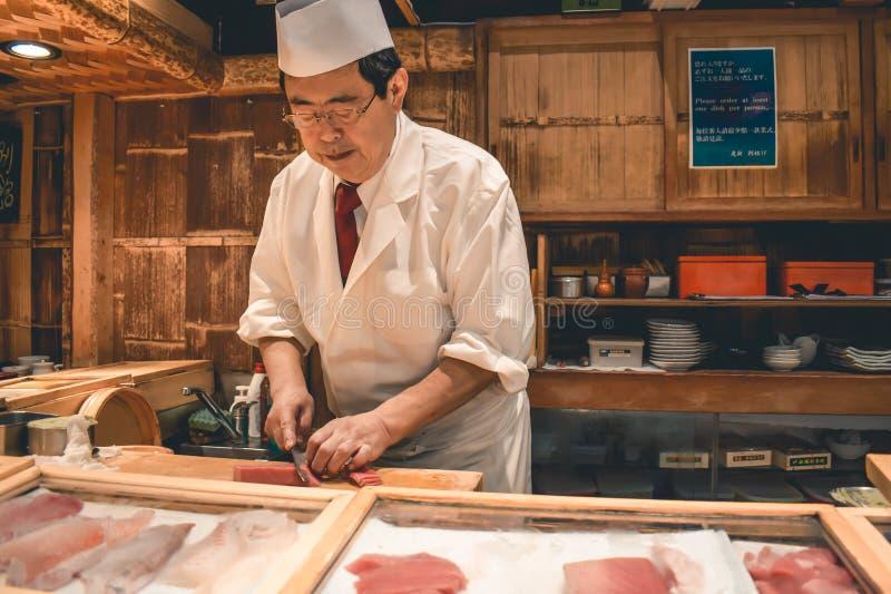 Sushi hoofdchef-kok die het verse ontbijt van de tonijnsashimi voorbereiden bij de Tsukiji-vissenmarkt in Tokyo stock foto's