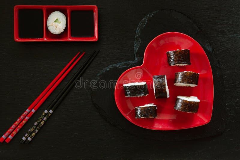Sushi japonês com molho de soja no prato do vermelho da forma do coração fotos de stock royalty free