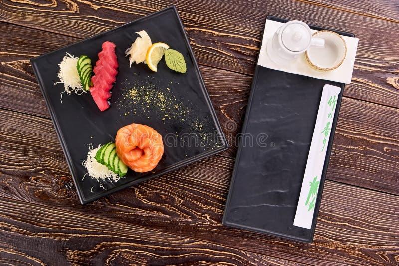 Sushi juisy fresco apetitoso en la placa negra cuadrada imagenes de archivo