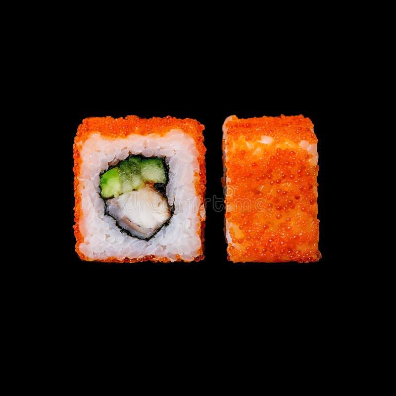 Sushi Kalifornien rulle med ålen, avokadot, gurkan och tobikoen som isoleras i svart bakgrund arkivfoton