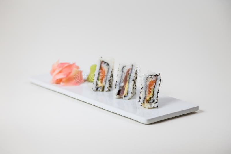 Sushi on a white plate on a white background and pickled ginger stock image