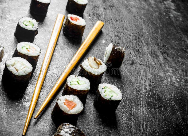 Sushi maki with chopsticks stock images