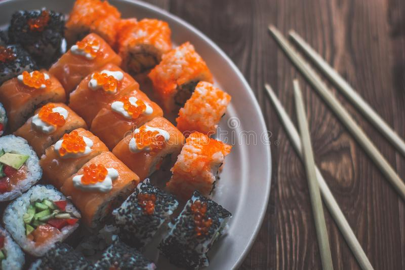 Sushi Maki Rolls con bastoni su una piastra di legno con Wasabi - vista dall'alto isolata sullo sfondo di legno grigio fotografia stock
