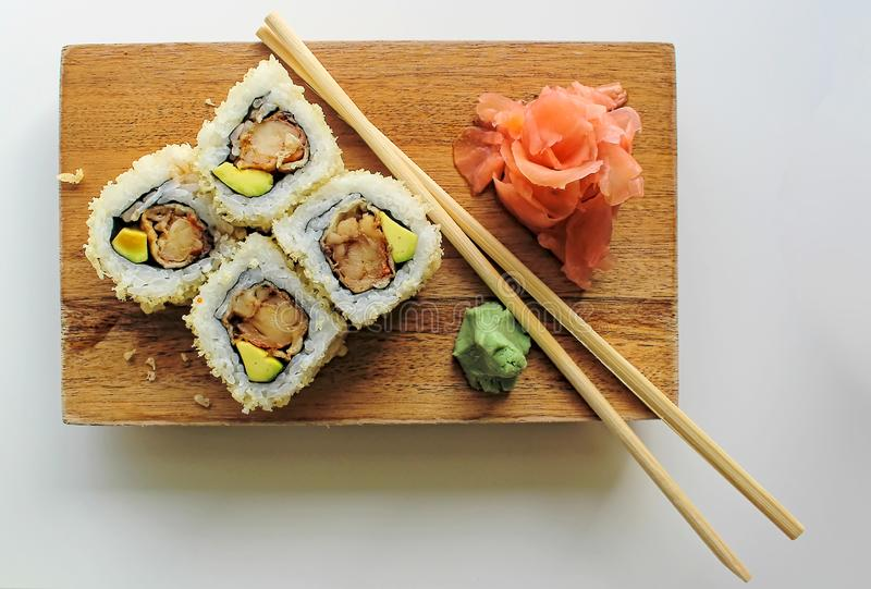 Sushi maki rolls with sesame seeds and avocado, with chopsticks, wasabi and ginger - close up view royalty free stock photo
