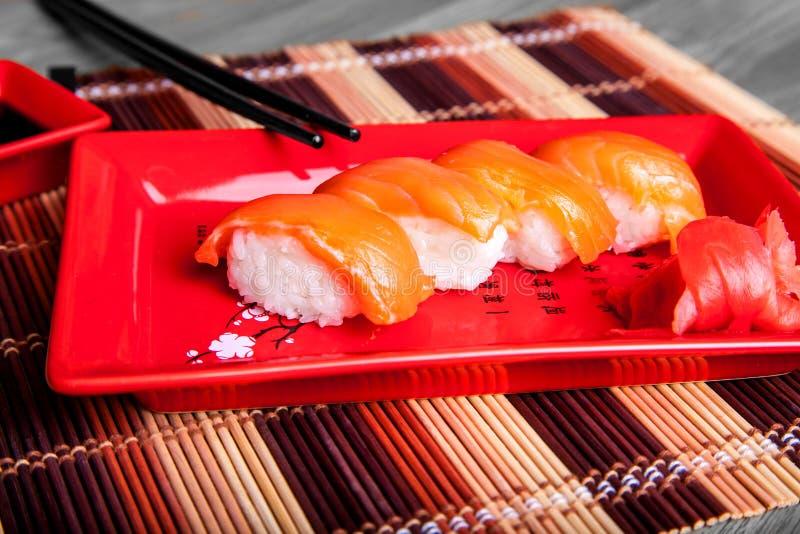 Sushi met zalm op rode plaat royalty-vrije stock afbeeldingen