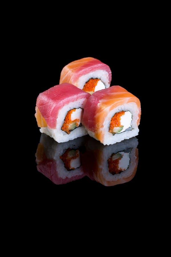Sushi mit Käse Philadelphia und tobiko auf einem schwarzen Hintergrund stockbild
