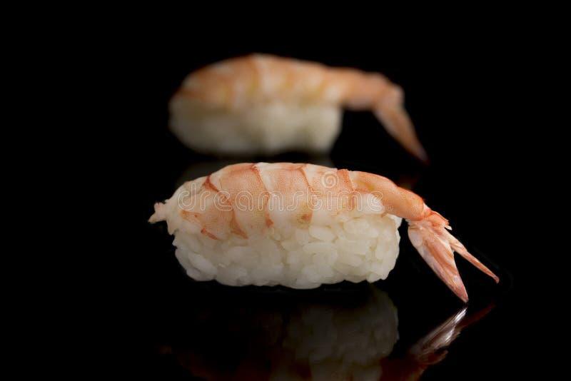 Sushi mit Langoustinegarnele, Minihummer auf einem schwarzen Hintergrund Japanische Küche ist ein Teller des Reises und der rohen stockbild
