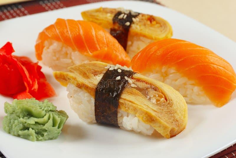 Sushi mit Omelett mit Aal und mit Lachsen und Ingwer und Wasabi auf schwarzem und rotem Bambusmattenabschluß oben stockbild